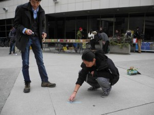 Jessica Tong and Alex Lu write powerful messages in chalk outside the UCC. Photo by Andrea Smith.