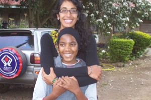 Supriya takes a picture with a smiling Tanzanian child.
