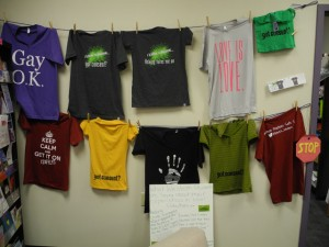 Consent awareness t-shirts from I Know Someone line the wall in the Peer Support office beneath the UCC.