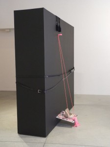 The big black box, girdled by belts and decorated with everyday objects  Photo by Patricia Barrett