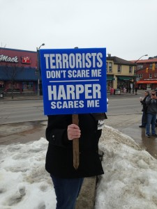 A protestor holds a sign while standing in Victoria Park on March 14th, 2015.  Photo by Sumayya Tobah.