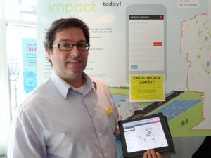 Jamie Skimming holds up a tablet showing an interactive map from reduceimpact.ca.